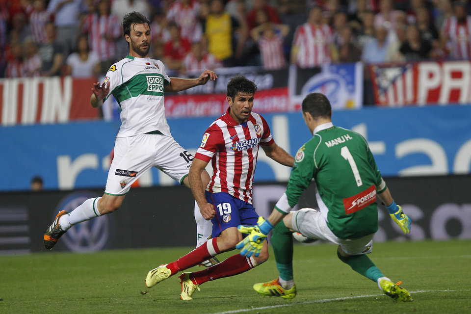 Photo - Atletico's Diego Costa, center, in action with Elche's goalkeeper Manu Herrera, right, during a Spanish La Liga soccer match between Atletico de Madrid and Elche at the Vicente Calderon stadium in Madrid, Spain, Friday, April 18, 2014. (AP Photo/Gabriel Pecot)