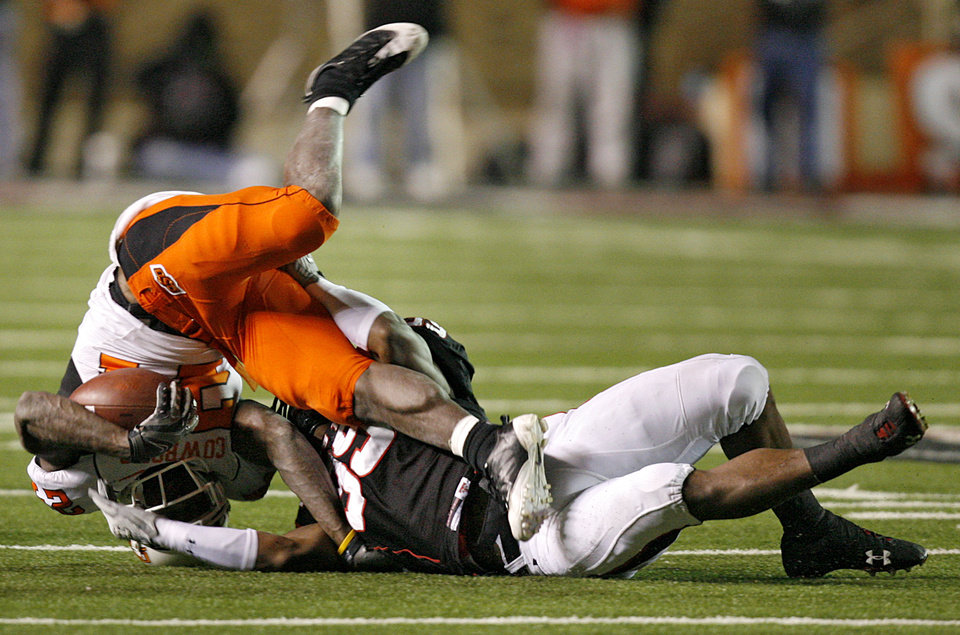 Photo - Oklahoma State's Kendall Hunter (24) is up ended by Texas Tech's Marlon Williams (39) during the second half of the college football game between the Oklahoma State University Cowboys (OSU) and the Texas Tech Red Raiders at Jones AT&T Stadium on Saturday, Nov. 8, 2008, in Lubbock, Tex.BY CHRIS LANDSBERGER/THE OKLAHOMAN