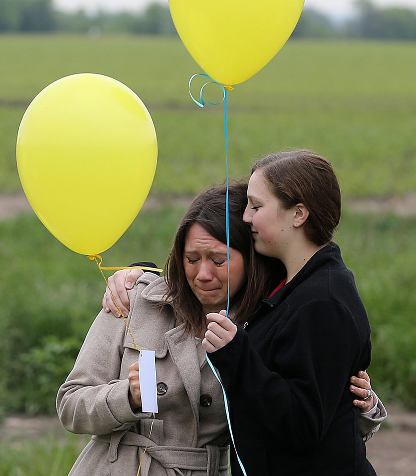 Photo - Abby Johnson, left, is comforted by Payton Landrum, right, before launching yellow balloons near the West Fertilizer Plant in memory of those who's lives were lost a year ago in the explosion, Thursday, April 17, 2014.  Fifteen people were killed, including 12 volunteer firefighters and others responding to the fire, and more than 200 were injured.   (AP Photo/Waco Tribune Herald, Jerry Larson)