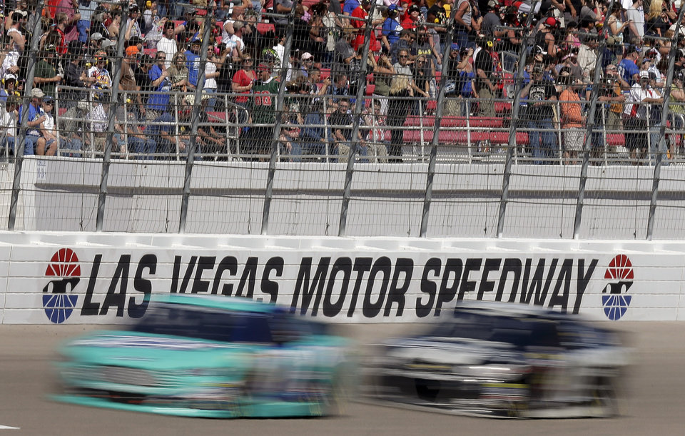 Photo - Drivers head into Turn 1 on the fourth lap of a NASCAR Sprint Cup Series auto race on Sunday, March 9, 2014, in Las Vegas. (AP Photo/Julie Jacobson)