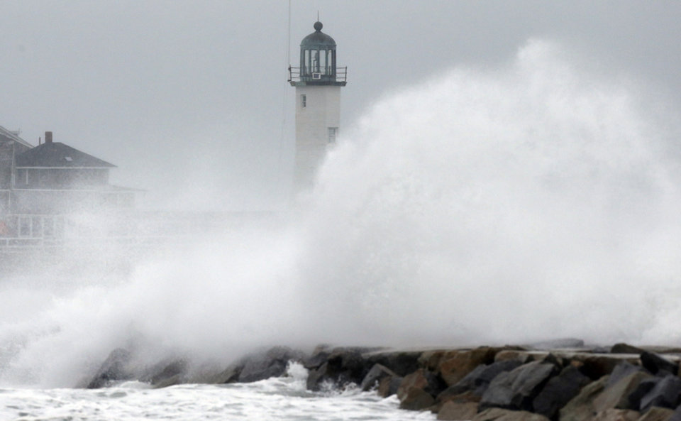Photo - Wind-driven waves crash on a sea wall in Scituate, Mass., Wednesday, March 26, 2014. Cape Cod and the islands were expected to bear the brunt of the spring storm that struck full force Wednesday. The storm could drop up to 10 inches of snow. (AP Photo/Michael Dwyer)
