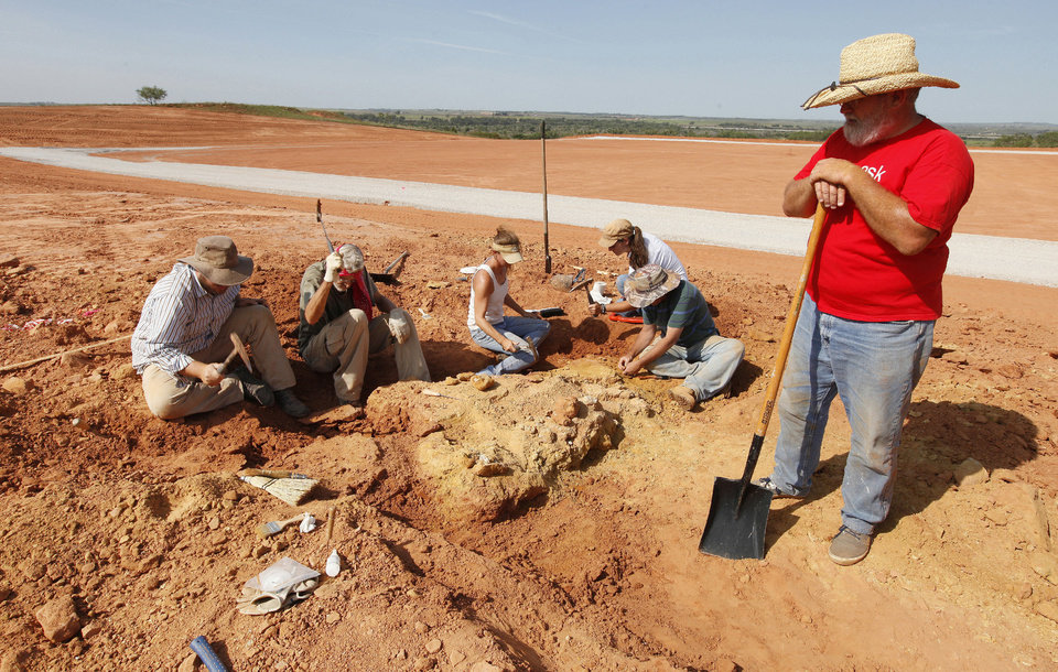 Photo - Paleontologist Kyle Davies, right, fossil preparator with the Sam Noble Oklahoma Museum of Natural History, looks on as archaeologists and paleontologists dig fossilized bones from pit C on an Apache Corp. drilling site at the Packsaddle Wildlife Management Area in Ellis County south of Arnett Thursday, Aug. 22, 2013.  Teeth and bone fossils found at the site included those from prehistoric camels and horses. Photo by Paul B. Southerland, The Oklahoman  PAUL B. SOUTHERLAND - PAUL B. SOUTHERLAND