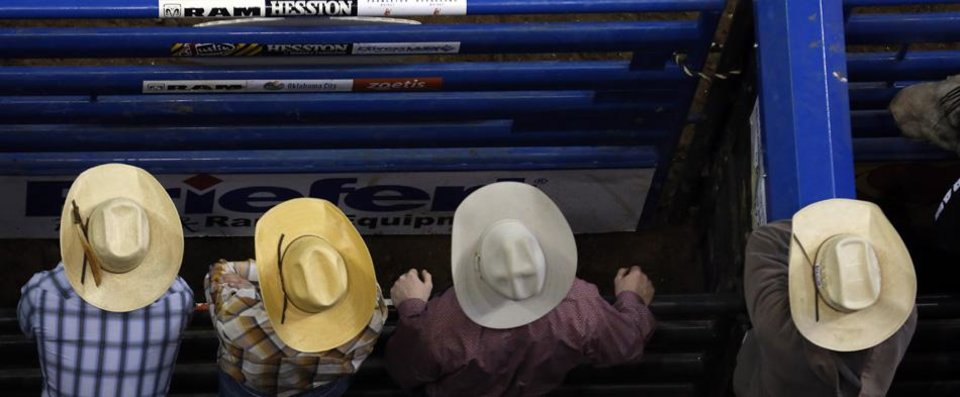 Cowboys watch the bareback riding at the National Circuit Finals Rodeo at the State Fair Arena in Oklahoma City, Friday, April 5, 2013. Photo by Sarah Phipps, The Oklahoman