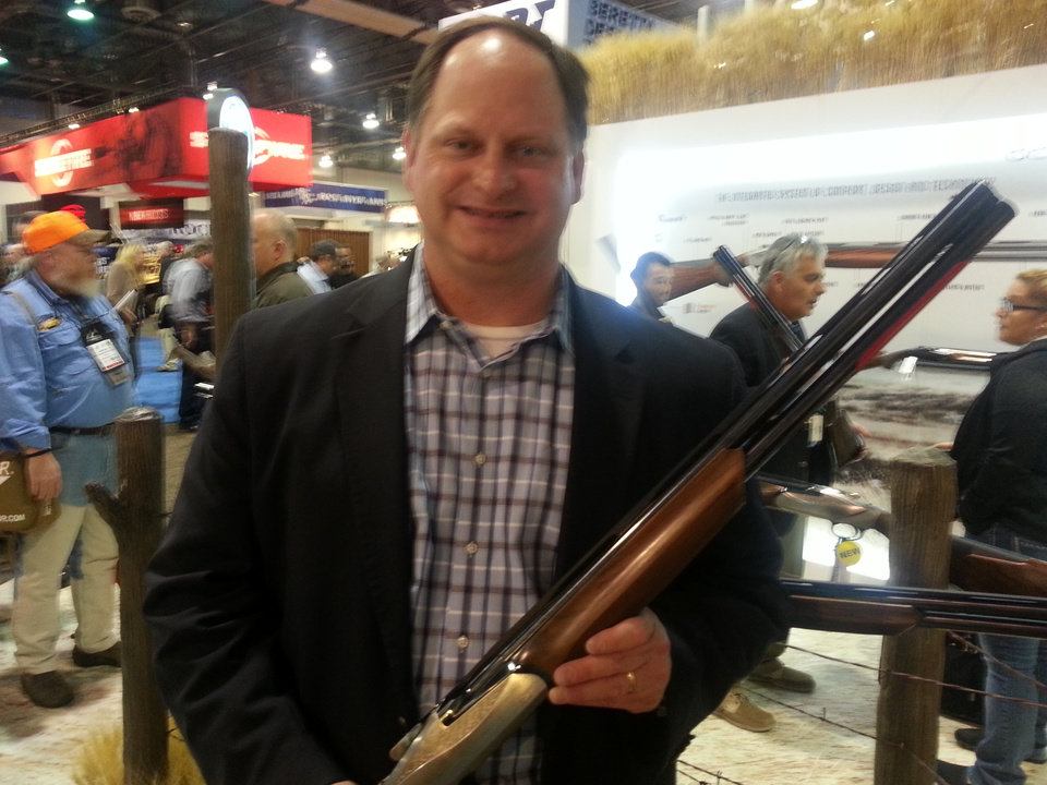 Photo -  Tom DeBolt, general manager of Benelli, holds the company's first over and under shotgun.