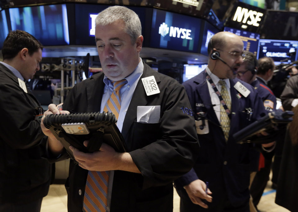 Photo - Trader Edward McCarthy, center, works on the floor of the New York Stock Exchange Thursday, March 13, 2014. Stocks opened higher as traders were encouraged by a pickup in retail sales and more signs of health in the U.S. job market. (AP Photo/Richard Drew)