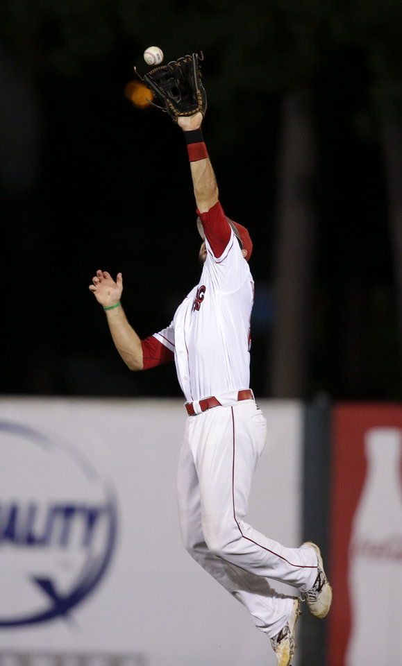 Photo - Louisiana Lafayette center fielder Seth Harrison (27) leaps for a bouncing grounder single by Mississippi's Errol Robinson in the second inning of an NCAA college baseball tournament super regional game in Lafayette, La.,Sunday, June 8, 2014. (AP Photo/Gerald Herbert)