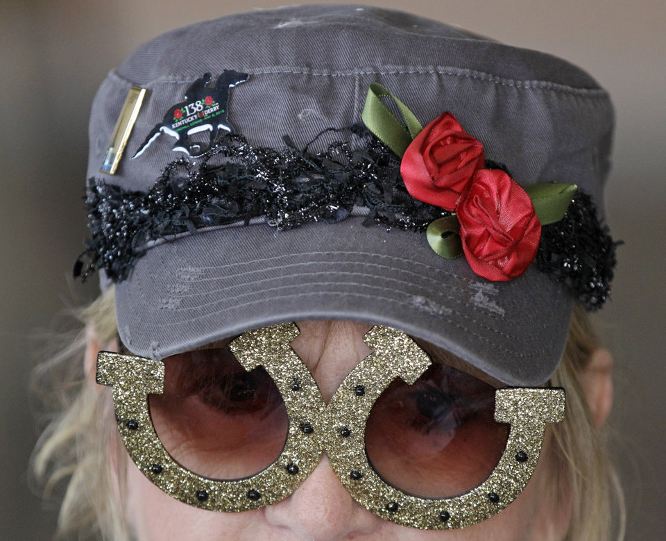 Photo - Sandy Cousins, Fond du Lac, Wis., wears horseshoe glasses while waiting for the 138th Kentucky Derby horse race at Churchill Downs Saturday, May 5, 2012, in Louisville, Ky.  (AP Photo/Mark Humphrey) ORG XMIT: DBY108