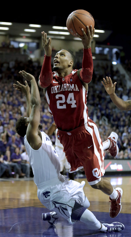 Photo - Oklahoma forward Romero Osby (24) puts up a shot under pressure from Kansas State forward Nino Williams (11) during the first half of an NCAA college basketball game Saturday, Jan. 19, 2013, in Manhattan, Kan. (AP Photo/Charlie Riedel) ORG XMIT: KSCR102