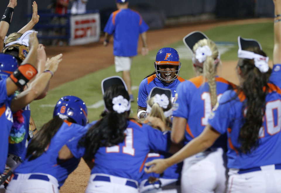 Florida's Briana Little is greeted at home after hitting a home run in the tenth inning during the Women's College World Series softball game between Nebraska and Florida at ASA Hall of Fame Stadium in Oklahoma City, Saturday, June, 1, 2013. Photo by Bryan Terry, The Oklahoman