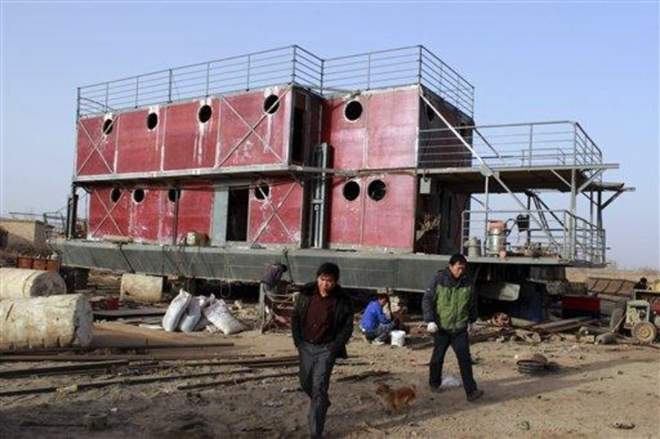 In this photo taken Nov. 24, 2012, Lu Zhenghai, right, walks near his ark-like vessel under construction in China's northwest Xinjiang Uyghur Autonomous Region.  Lu Zhenghai is one of at least two men in China predicting a world-ending flood, come Dec. 21, the fateful day many believe the Maya set as the conclusion of their 5,125-year long-count calendar. Zhenghai has spent his life savings building the 70-foot-by-50-foot vessel powered by three diesel engines, according to state media. In Mexico's Mayan heartland, nobody is preparing for the end of the world; instead, they're bracing for a tsunami of spiritual visitors. (AP Photo/ANPF-Chen Jiansheng)