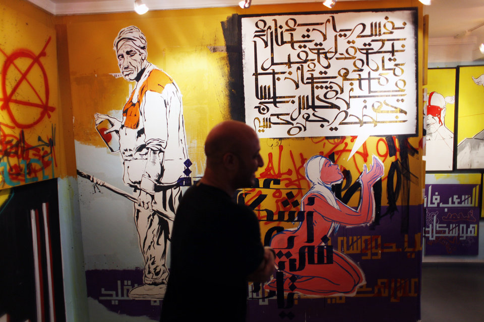 "In this Thursday, Oct. 4, 2012 photo, an Egyptian man inspects a mural with Arabic that reads ""God, give me justice,"" inside an art exhibition for street graffiti in Cairo, Egypt. Graffiti has been among the most powerful art forms and tools of Egypt's revolution and the turbulent months since, but it also has proven to be its most vulnerable and ephemeral. So a group of artists, photographers and a publisher joined hands to preserve the images. ""Wall Talk"" _ their newly released, 680-page book _ collects hundreds of photos of graffiti dating from the Jan. 25, 2011 eruption of the revolt against then-President Hosni Mubarak until today. (AP Photo/Nasser Nasser)"