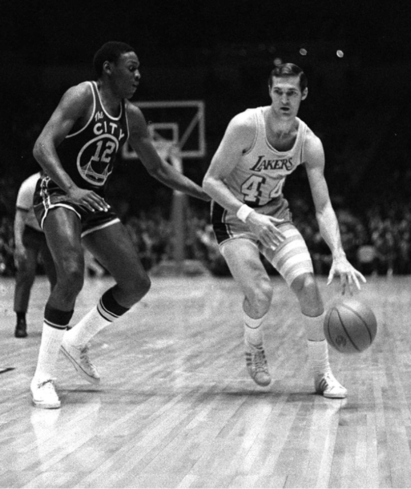 Photo - FILE--Los Angeles Lakers guard Jerry West drives the ball past San Francisco Warriors' Ron Williams March 11, 1970 in Los Angeles. West, part of seven NBA championships in four decades as a player, coach and executive with the Lakers, will retire Monday, August 7, 2000. The Los Angeles Times, citing unidentified league and team sources, said West, now executive vice president, will continue as a consultant. (AP Photo/file)