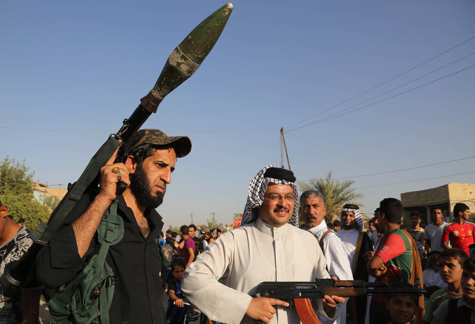 Photo - Iraqi Shiite tribal fighters pose with their weapons in Baghdad's Sadr city, Iraq, Saturday, June 14, 2014. Thousands of Shiites from Baghdad and across southern Iraq answered an urgent call to arms Saturday, joining security forces to fight the Islamic militants who have captured large swaths of territory north of the capital and now imperil a city with a much-revered religious shrine. (AP Photo/Karim Kadim)