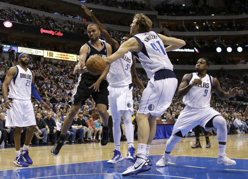 Photo - San Antonio Spurs' Tony Parker, second from left, of France, passes the ball from beneath the basket as Dallas Mavericks' Dirk Nowitzki (41), of Germany, defends in the second half of an NBA basketball game on Friday, Jan. 25, 2013, in Dallas. Mavericks' Vince Carter (25), Bernard James (5) and Jae Crowder (9) help on the play in the 113-107 Spurs win. (AP Photo/Tony Gutierrez)