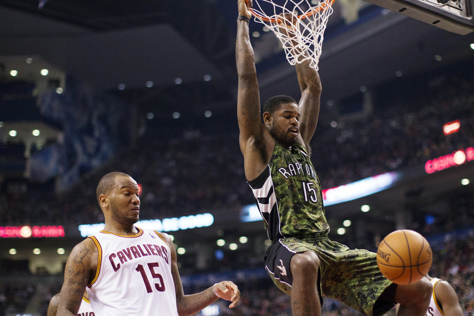 Toronto Raptors'  Amir Johnson, right, hangs from the rim after scoring on Cleveland Cavaliers' Marreese Speights during the first half of an NBA basketball game, Saturday, Jan. 26, 2013, in Toronto. (AP Photo/The Canadian Press, Chris Young)