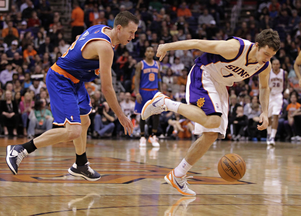 New York Knicks' Steve Novak, left, and  Phoenix Suns' Goran Dragic (1), of Slovenia, chase down a loose ball during the first half of an NBA basketball game on Wednesday, Dec. 26, 2012, in Phoenix. (AP Photo/Matt York)