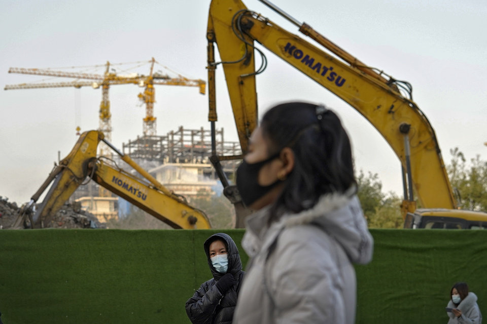 Photo -  Women wearing face masks to help curb the spread of the coronavirus walk by machinery dismantling buildings during the morning rush hour in Beijing, Tuesday, Dec. 1, 2020. (AP Photo/Andy Wong)