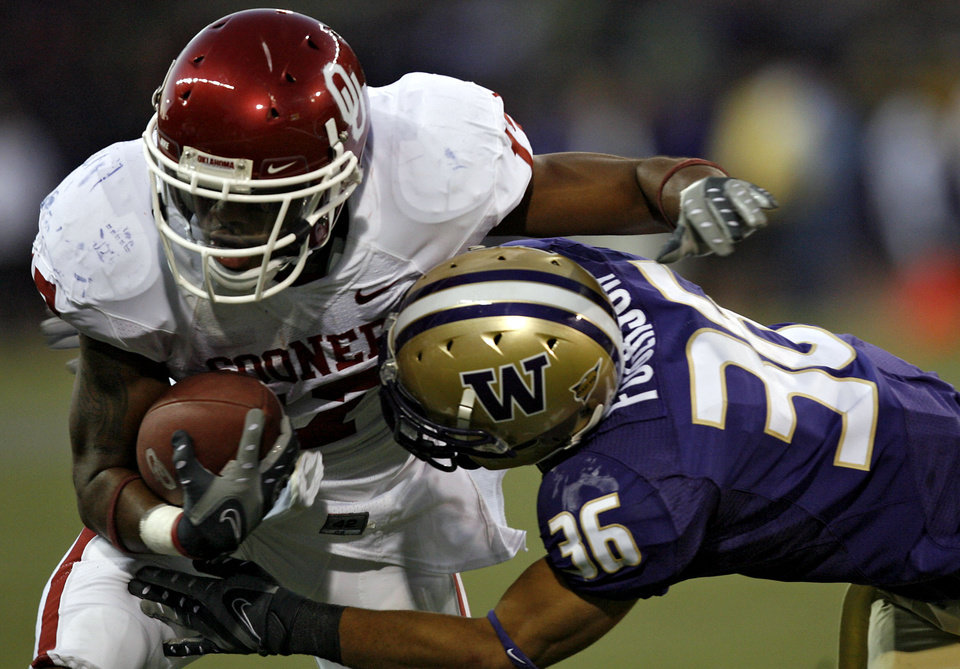 Photo - Oklahoma's Mossis Madu (17) is brought down by Washington's Johri Fogerson (36) during the second half of the college football game between the University of Oklahoma Sooners (OU) and the University of Washington Huskies (UW) at Husky Stadium on Saturday, Sep. 13, 2008, in Seattle, Wash. 