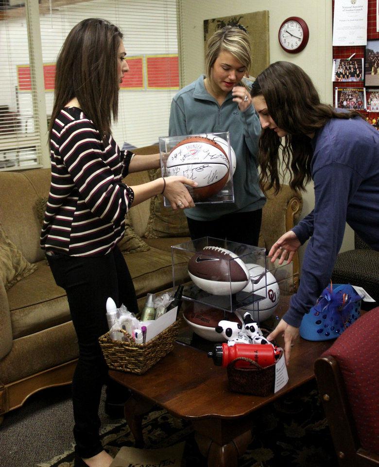 Putnam City North students, from left, Kate Sleem, Kourtney Hatcher and Anna Burch sort through items donated for a silent auction. The event will raise money for the Make-A-Wish Foundation to help wishes come true for two young children with life-threatening illnesses. PHOTO BY MOLLY JAMES, FOR THE OKLAHOMAN      <strong></strong>
