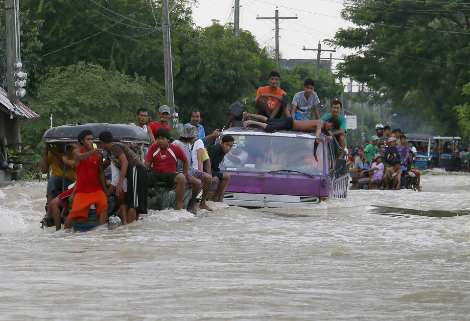 Photo - Commuters ride a farm tractor as it maneuvers through strong floodwaters along a highway in La Paz township, Tarlac province in northern Philippines Tuesday, Oct. 20, 2015. Two days after Typhoon Koppu battered northern Philippines residents begin cleaning up their muddied homes. (AP Photo/Bullit Marquez)