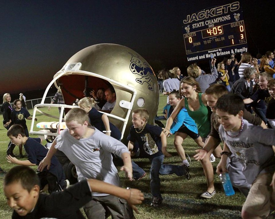 "Kingfisher students and a customized golf cart called ""The Helmet,"" lead the high school football team onto the field before the YellowJackets play Bethany during their high school football game in Kingfisher, Oklahoma on Friday, Oct. 14, 2011. Photo by John Clanton, The Oklahoman"