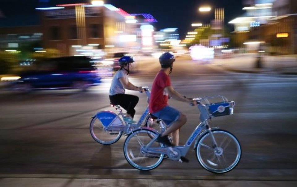 Photo -  Spokies, bike rental stations operated by EMBARK, have added to the interest in cycling downtown. Two riders on Spokies are shown riding east on Reno Avenue in Bricktown. [Doug Hoke, The Oklahoman Archives]