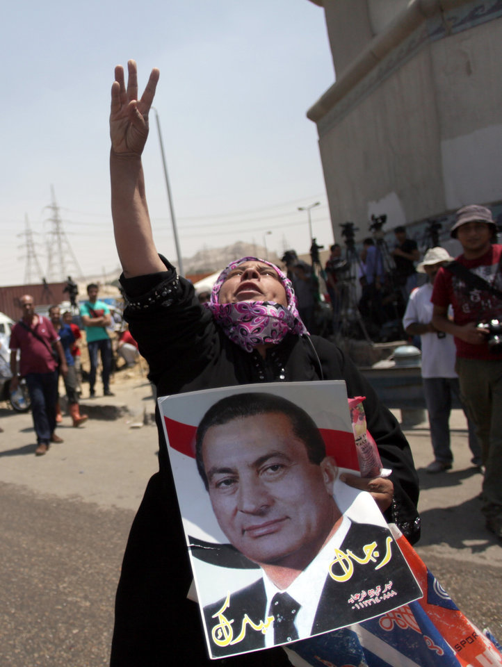 Photo - A supporter of Egypt's deposed autocrat Hosni Mubarak holds a poster of him and chants slogans in front of Tora prison where he is held, in Cairo, Thursday, Aug. 22, 2013. Mubarak is expected to be freed from prison and placed under house arrest on Thursday after being ordered released the previous day, following more than two years in detention. The Arabic writing on the poster reads,