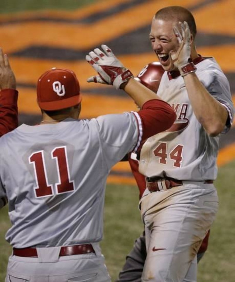 Photo - OU's Austin O'Brien celebrates after scoring in the 18th inning of a Bedlam baseball game between Oklahoma State University and the University of Oklahoma in Stillwater, Tuesday, April 15, 2014. Photo by Bryan Terry, The Oklahoman
