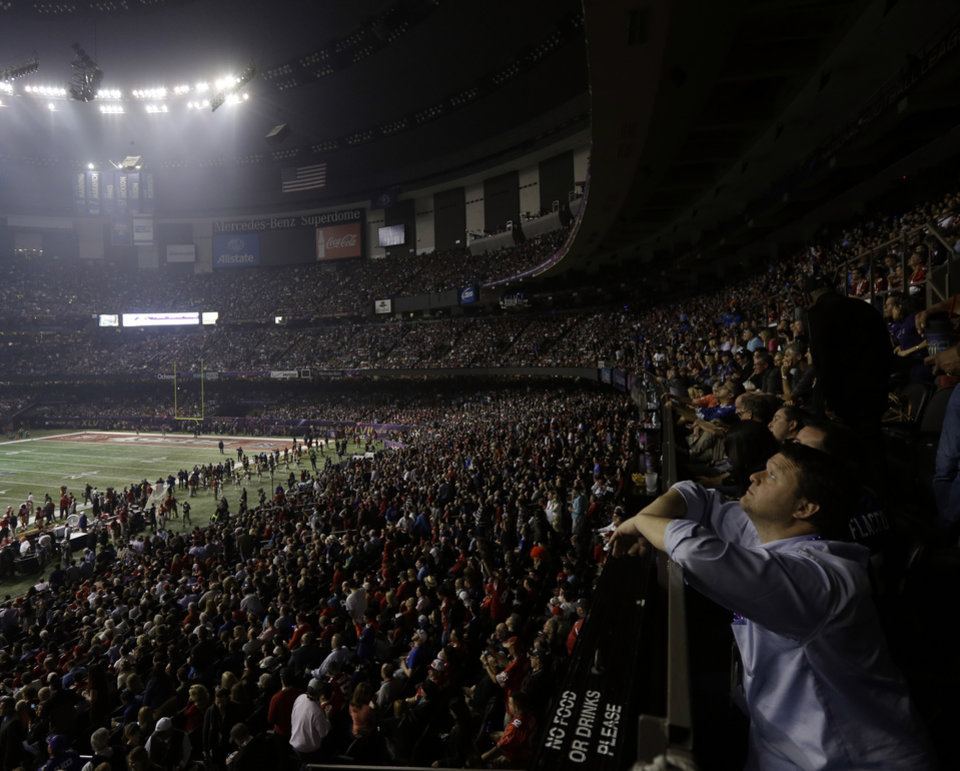 Photo - A fan looks around the Superdome after half the lights went out during a power outage in the second half of the NFL Super Bowl XLVII football game between the San Francisco 49ers and Baltimore Ravens on Sunday, Feb. 3, 2013, in New Orleans. (AP Photo/Gerald Herbert)