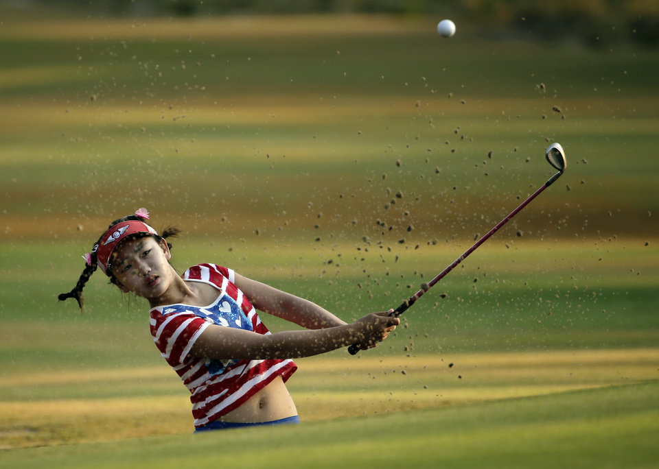 Photo - Lucy Li hits from a sand trap on the 10th hole during the first round of the U.S. Women's Open golf tournament in Pinehurst, N.C., Thursday, June 19, 2014. (AP Photo/Chuck Burton)