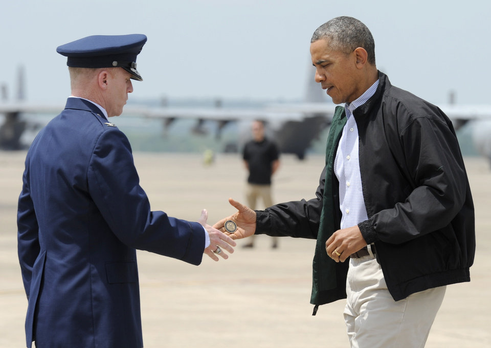 Photo - President Barack Obama shakes hands with Col. Patrick Rhatigan, Commander, 19th Airlift Wing & Little Rock AFB, left, and give him a challenge coin after Obama arrives at Little Rock Air Force Base, Ark., Wednesday, May 7, 2014. Obama is visiting with first responders and families affected by the recent tornados. (AP Photo/Susan Walsh)