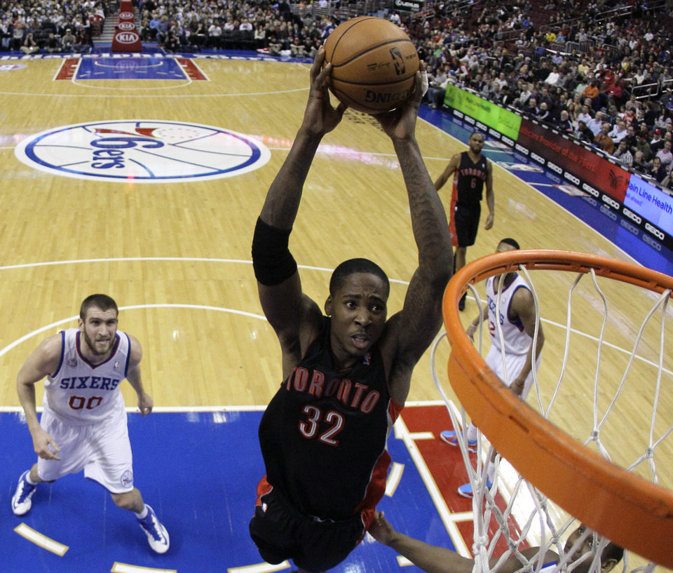Toronto Raptors' Ed Davis, center, goes up for a dunk as Philadelphia 76ers' Spencer Hawes looks on during the first half of an NBA basketball game on Friday, Jan. 18, 2013, in Philadelphia. (AP Photo/Matt Slocum)