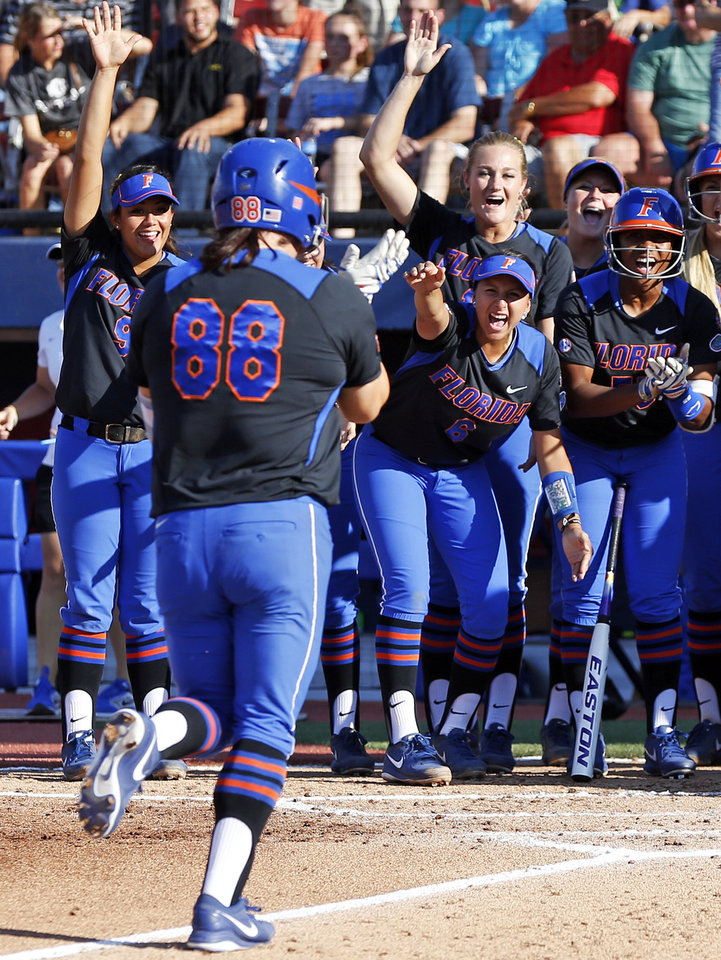 Photo - The Florida Gators celebrate a home run by Bailey Castro (88) in the 2nd inning during Game 5 of the Women's College World Series softball tournament between Florida and Oregon at ASA Hall of Fame Stadium in Oklahoma City, Friday, May 30, 2014. Photo by Nate Billings, The Oklahoman