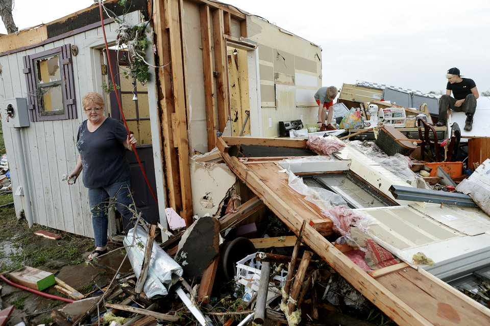 Photo - Marlena Hodson walks out of her home as her grandsons, Campbell Miller, 10, and Dillon Miller, 13, at right, help her sort through belongings after a tornado damaged her home Carney Okla., on Sunday, May 19, 2013. Hodson and her family left the home to escape the tornado. (AP Photo/The Oklahoman, Bryan Terry)