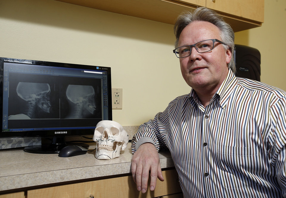 Photo - Dr. Steven Sullivan uses models and X-rays to explain corrective jaw surgery.  Photo by Sarah Phipps, The Oklahoman