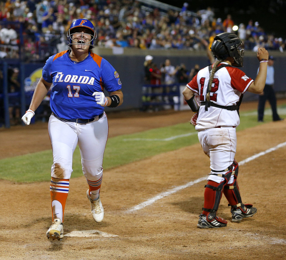 Florida's Lauren Haeger reacts as she scores past Nebraska's Taylor Edwards in the fifteenth inning during the Women's College World Series softball game between Nebraska and Florida at ASA Hall of Fame Stadium in Oklahoma City, Saturday, June, 1, 2013. Photo by Bryan Terry, The Oklahoman
