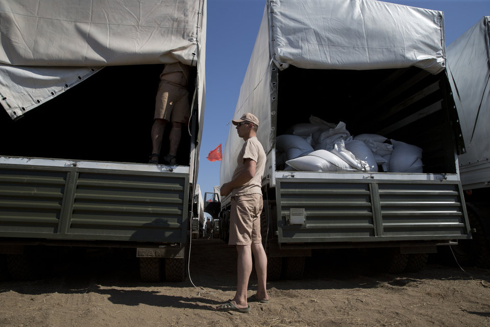 Photo - CORRECTS NAME OF TOWN TO KAMENSK-SHAKHTINSKY. A driver stands near trucks as an aid convoy is parked in Kamensk-Shakhtinsky, Russia, Friday, Aug. 15, 2014. The Ukrainian government threatened to use all means available to block the convoy if the Red Cross was not allowed to inspect the cargo. Such an inspection would ease concerns that Russia could use the aid shipment as cover for a military incursion in support of the separatists, who have come under growing pressure from government troops. (AP Photo/Pavel Golovkin)