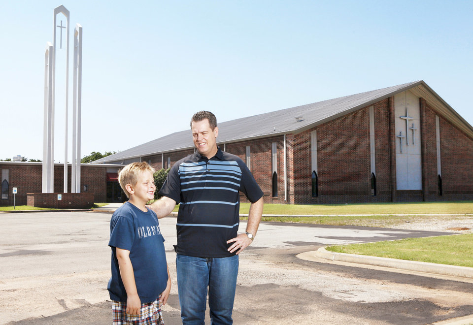 Photo - The Rev. Steve Eden, senior pastor of Grace Church, stands in front of the church at 100 S Choctaw Road with his son Joshua, 9. Photo by Jim Beckel, THE OKLAHOMAN