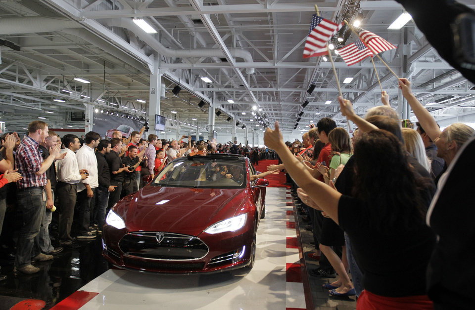 Tesla workers cheer one of the first Tesla Model S cars sold during a rally June 22 at the Tesla factory in Fremont, Calif.  AP Archives Photo