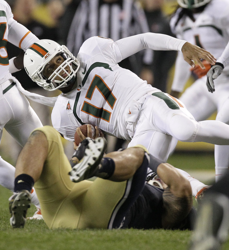 Photo -   Miami quarterback Stephen Morris (17) is tackled by Notre Dame linebacker Manti Te'o during the second half of an NCAA college football game at Soldier Field, Saturday, Oct. 6, 2012, in Chicago. (AP Photo/Nam Y. Huh)
