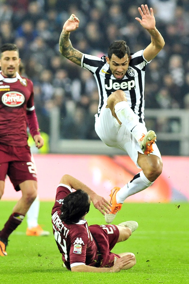 Photo - Juventus forward Carlos Tevez, of Argentina,  jumps Torino defender Emiliano Moretti during a Serie A soccer match between Juventus and Torino at the Juventus stadium, in Turin, Italy, Sunday, Feb. 23, 2014. (AP Photo/Massimo Pinca)