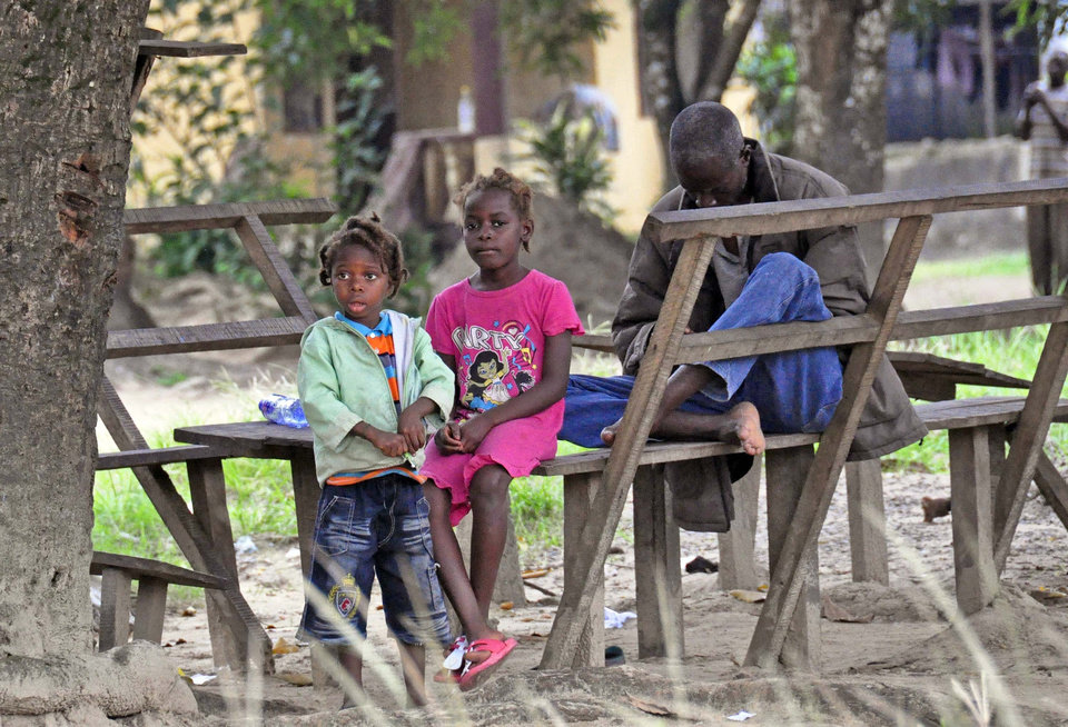 Photo - In this photo taken on Saturday, Aug. 16, 2014, a family sit near the body of their mother suspected of dying from the Ebola virus, as the father, right, tries to contact family members on his mobile phone, in Monrovia, Liberia. Liberian officials fear Ebola could soon spread through the capital's largest slum after residents raided a quarantine center for suspected patients and took items including blood-stained sheets and mattresses. The violence in the West Point slum occurred late Saturday and was led by residents angry that patients were brought from other parts of the capital to the holding center, Tolbert Nyenswah, assistant health minister, said Sunday. (AP Photo/Abbas Dulleh)