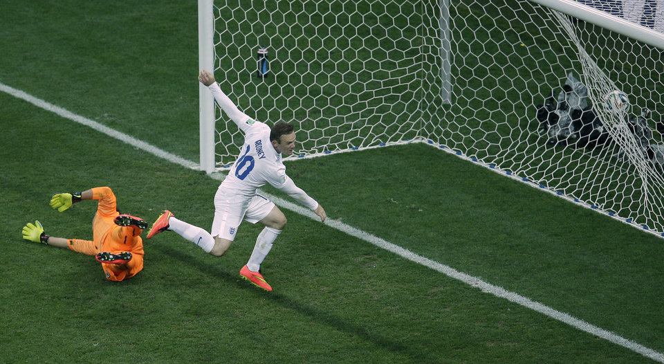 Photo - England's Wayne Rooney, center, celebrates scoring his side's first goal past Uruguay's goalkeeper Fernando Muslera, left, during the group D World Cup soccer match between Uruguay and England at the Itaquerao Stadium in Sao Paulo, Brazil, Thursday, June 19, 2014.  (AP Photo/Michael Sohn)