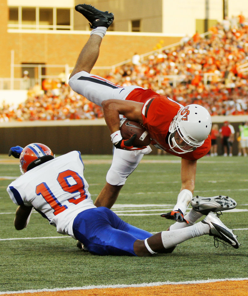 Photo - OSU's Charlie Moore (17) is tripped up by Savannah State's Jovante Miller (19) during a college football game between Oklahoma State University (OSU) and Savannah State University at Boone Pickens Stadium in Stillwater, Okla., Saturday, Sept. 1, 2012. Photo by Nate Billings, The Oklahoman