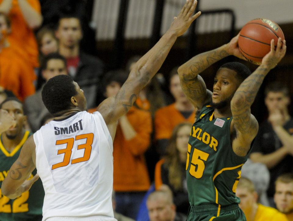 Baylor guard Pierre Jackson, right, looks past Oklahoma State guard Marcus Smart, left, for an open teammate during the second half of an NCAA college basketball game in Stillwater, Okla., Wednesday, Feb. 6, 2013. Jackson scored 24 points in the 67-69 loss to Oklahoma State. (AP Photo/Brody Schmidt)