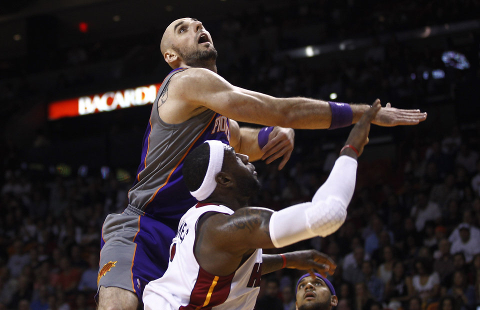 Phoenix Suns' Marcin Gortat (4) watches the ball after trying to block a shot by Miami Heat's LeBron James during the first half of an NBA basketball game in Miami, Monday, Nov. 5, 2012. (AP Photo/J Pat Carter)