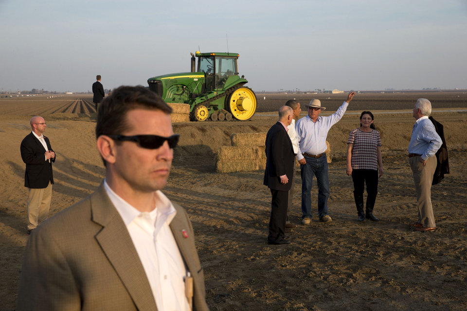 Photo - President Barack Obama, second from left in group, tours a local farm with Governor Jerry Brown, left, Joe Del Bosque of Empresas Del Bosque, Inc., and Maria Gloria Del Bosque also of Empresas Del Bosque, Inc.,and Rep. Jim Costa, D-Calif., in Los Banos, Calif., Friday, Feb. 14, 2014, where he spoke about the drought. (AP Photo/Jacquelyn Martin)