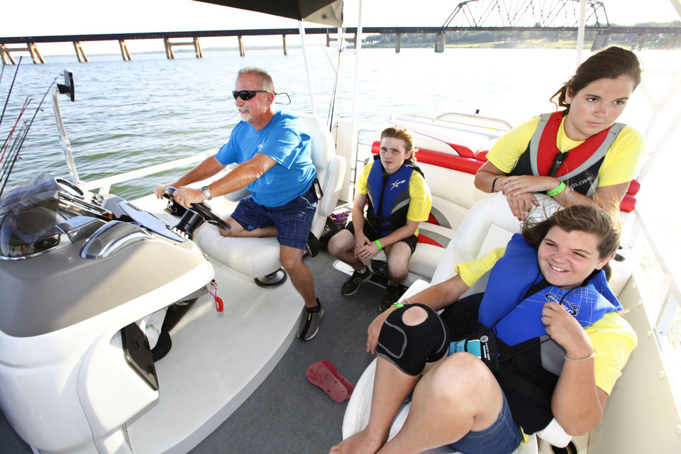 Stewart Matheson, at the wheel, Jimmy Turner, 16, and sisters Alyssa Beck, 15, and  Brianna Beck, 16, seated, head out for a day of fishing during Camp Cavett at Lake Texoma.  <strong>David McDaniel - The Oklahoman</strong>