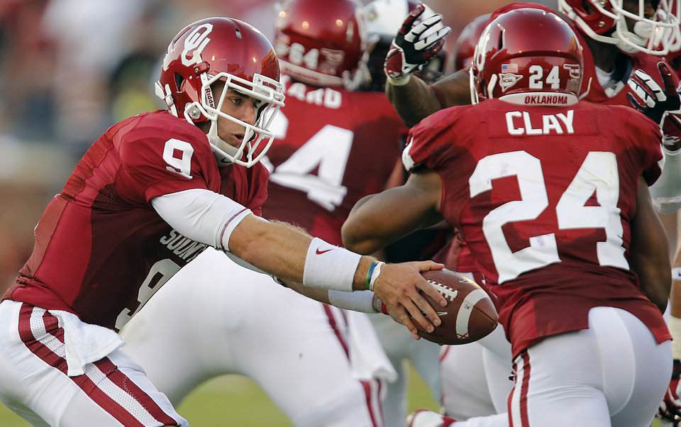 Photo - Oklahoma's Trevor Knight (9) hands the ball off to Brennan Clay (24) during the college football game between the University of Oklahoma Sooners (OU) and the University of Louisiana Monroe Warhawks (ULM) at the Gaylord Family Memorial Stadium on Saturday, Aug. 31, 2013 in Norman, Okla.  Photo by Chris Landsberger, The Oklahoman
