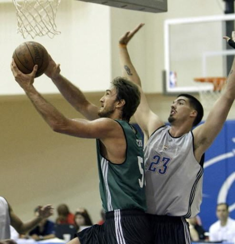 Photo - Boston Celtics' Semih Erden, left, of Turkey gets off a shot in front of Oklahoma City Thunder's  Byron  Mullens during the second half of an NBA summer league basketball game in Orlando, Fla., Monday, July 5, 2010.(AP Photo/John Raoux)